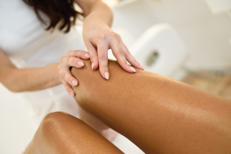 Beauty massage in the leg in a beauty salon. Beautician giving a massage with oil on the skin.