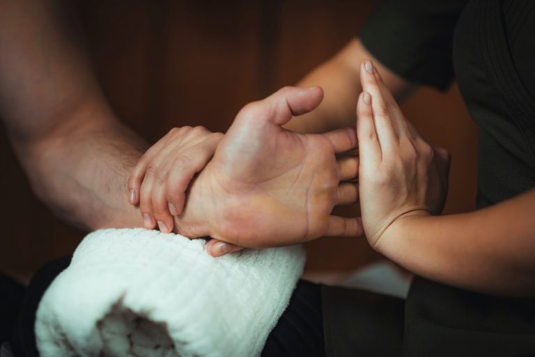 Physiotherapist massaging male patient with injured hand muscle. Sports injury treatment.