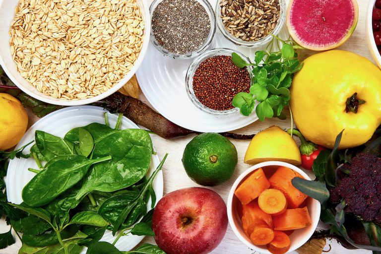 Set of organic healthy diet food, superfoods - beans, legumes, nuts, seeds, greens, fruit and vegetables on white background, copy space. Top view, frame, flat lay.