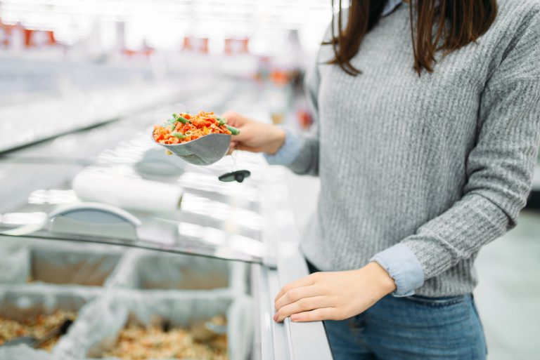 Woman picks up a package of frozen vegetables in a supermarket, family shopping. Female customer buys products in shop
