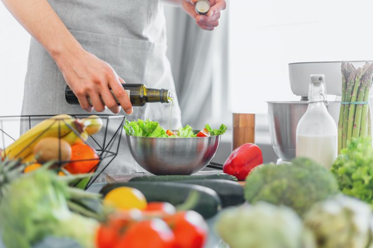 Young man chef cook cooking healthy meal salad with vegetables in the kitchen. Lifestyle background. Horizontal
